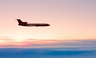 Daybreak. Passenger airplane silhouette on the morning-glow background.